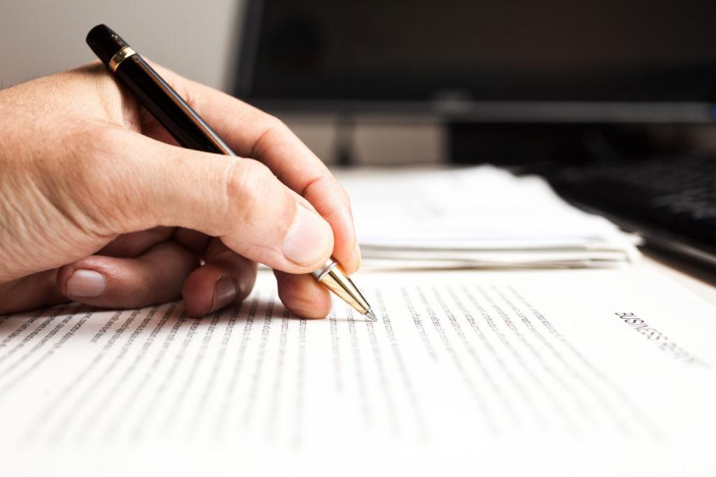 Hand mit Stift auf Papier