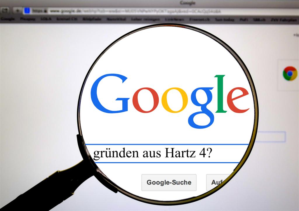 """Eine Lupe vergrößert das Google-Suchfeld, in dem """"gründen aus Hartz 4"""" steht"""