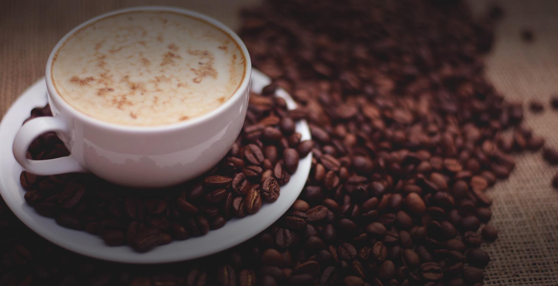 Kaffeebohnen neben einer Tasse Kaffee