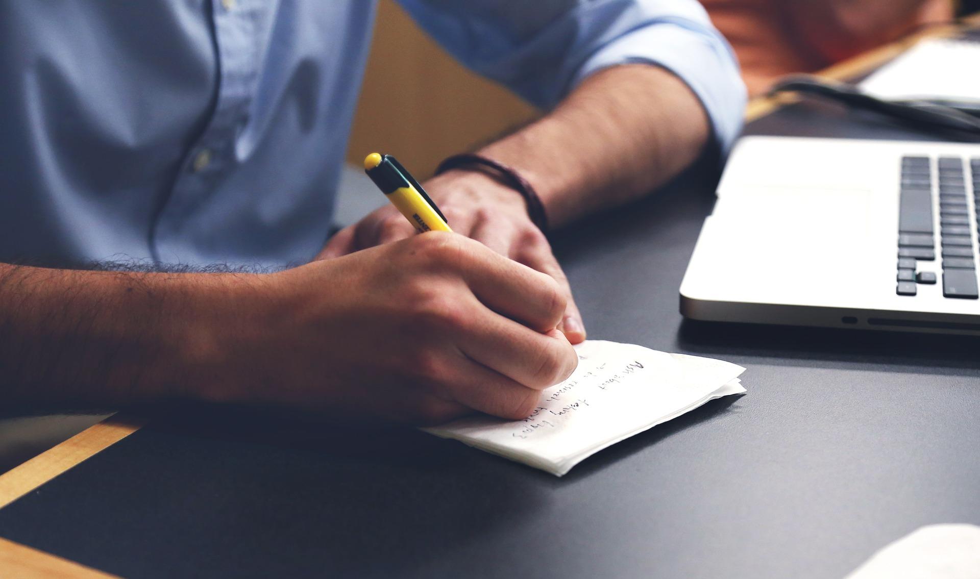 Mann schreibt am Arbeitsplatz
