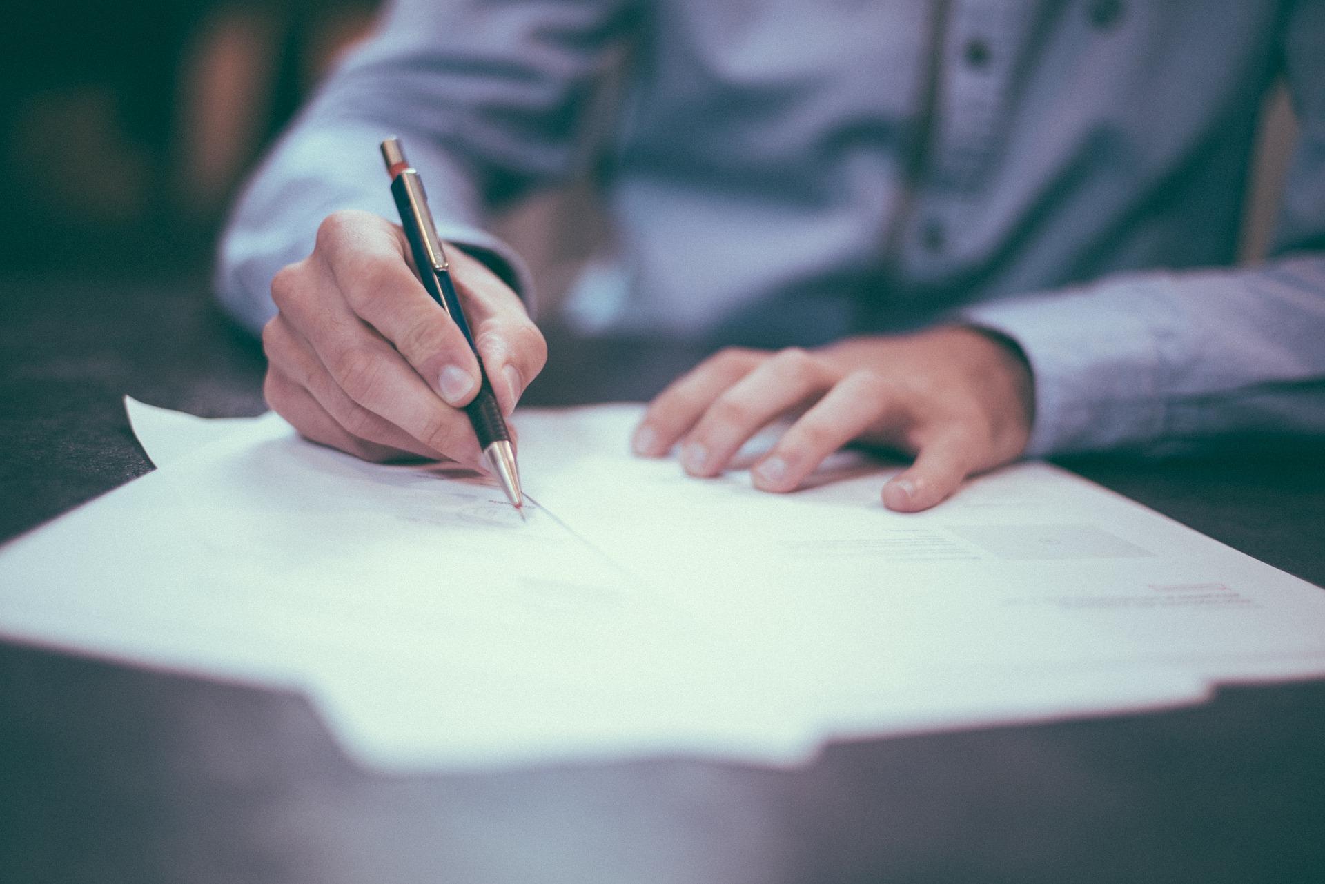 Ein Mann mit Stift unterschreibt einen Vertrag