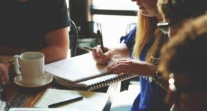 Drei junge Leute sitzen an einem Tisch und arbeiten