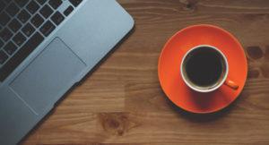 Eine Tasse mit Kaffee steht neben einem Laptop