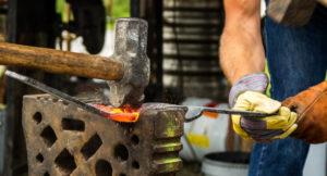 Ein Schmied bearbeitet eine Eisenstange