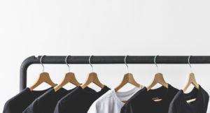 Viele Kleider hängen auf Bügeln auf einer Kleiderstange.