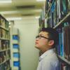 Ein Mann steht im Gang einer Bibliothek