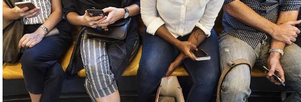 Menschen mit Handys in der Hand sitzen in der Bahn