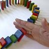 Reihe von Dominosteinen, die durch eine Hand unterbrochen wird.