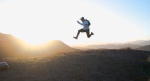 Ein Mann springt über Hügel bei Sonnenuntergang.