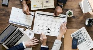 Aufnahme eines Kalenders auf einem Schreibtisch mit zwei sitzenden Menschen.