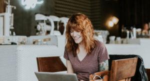 Eine Frau sitzt vor ihrem Laptop und lächelt