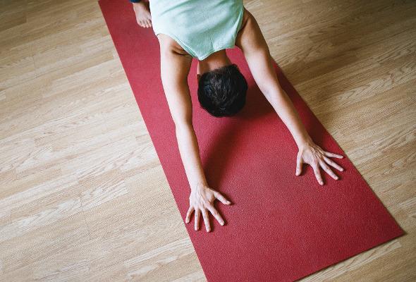 Frau sitzt auf einer roten Yogamatte