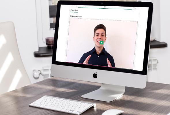Aufnahme von einem Rechner. Auf dem Bildschirm ist ein Video mit einem Mann zu sehen.