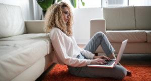 Eine Frau sitzt auf dem Boden mit ihrem Laptop.