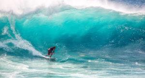 Ein Mann surft auf einer sehr großen Welle.