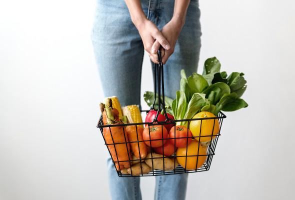 Eine Frau trägt einen Lebensmittelkorb