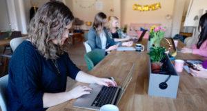 Zwei Frauen sitzen mit ihren Laptops an einem Holztisch.