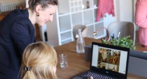 Zwei Frauen sitzen am Tisch mit einem Laptop.