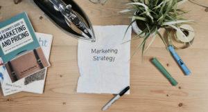 Schreibtisch mit einem Blatt auf dem steht Marketing Strategy