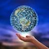 Ein Mensch hält eine Weltkugel in der Hand. Auf dieser sind viele Verknüpfungspunkte abgebildet.