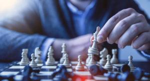 Ein Mann rückt Schachfiguren auf einem Schachbrett.