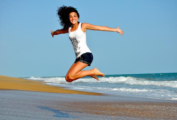 Frau springt an einem Strand in die Luft.