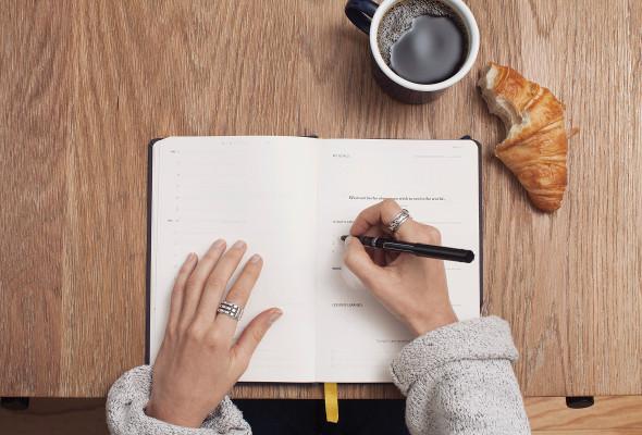 Eine Frau schreibt etwas in einen Kalender . Ein Kaffe sowie Gebäck liegt daneben.