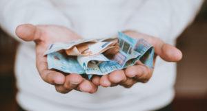 Mann hält Geldscheine in seiner Hand und streckt diese nach vorne.