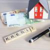 Ein Miniaturhaus, ein Kugelschreiber, Geldscheine und Scrabble-Steine mit dem Wort Kredit liegen auf einem Tisch.