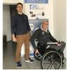 Ein Mann sitzt im Rollstuhl. Ein weiterer Mann steht dahinter.