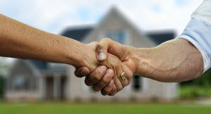 Zwei Menschen reichen sich die Hand. Im Hintergrund ist ein großes Haus zu sehen.