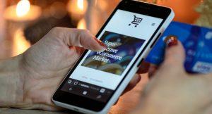 Eine Frau hält ein Handy in der Hand. Auf dem Bildschirm ist ein Online-Shop zu zu sehen.