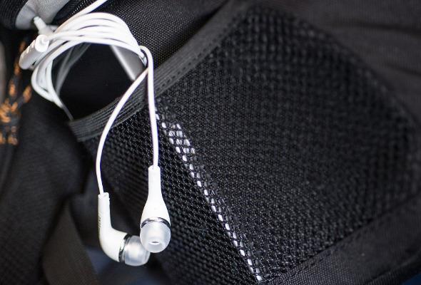 Weiße Kopfhörer schauen aus der Tasche raus.