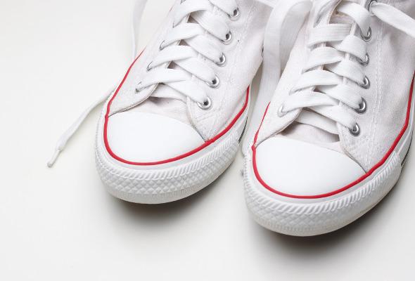 Weiße Turnschuhe stehen auf einem weißen Boden.