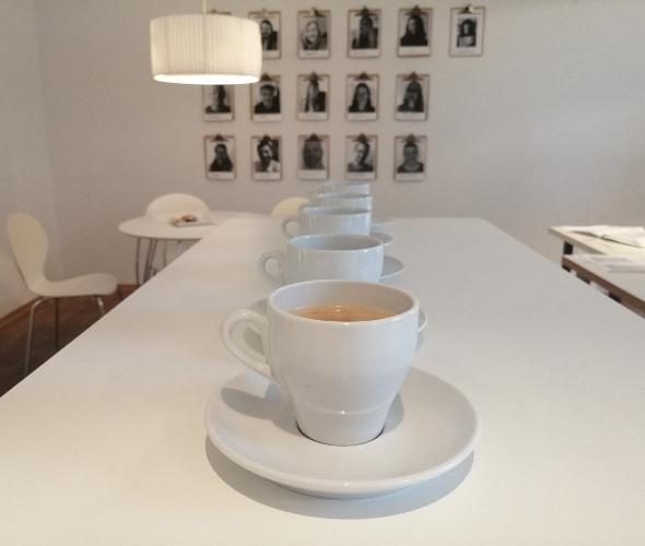 Mehrere Kaffeetassen stehen hintereinander. Im Hintergrund hängen Fotos von Mitarbeitern in schwarz weiß,