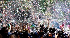 Feiernde Menschen stehen im Vordergrund während in der Luft buntes Konfetti fliegt.