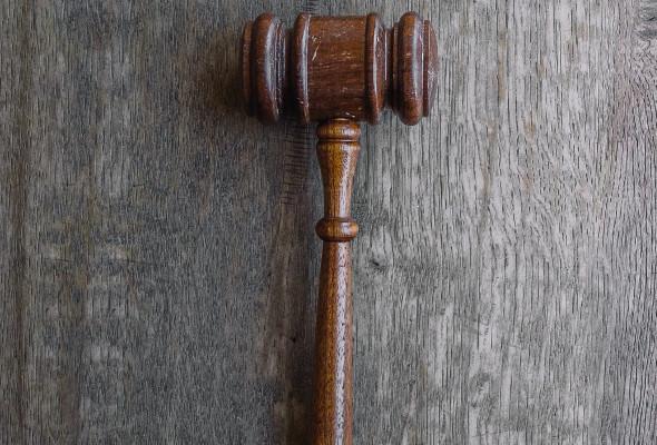 Ein Richterhammer liegt auf schwarzem Untergrund.