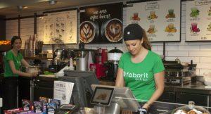 Eine Frau mit grünem Shirt steht hinter der Theke und verkauft Eis.