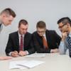 Vier Männer schauen sich einen Zettel an, der auf dem Tisch liegt.