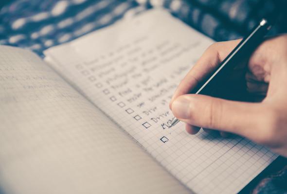 Eine Person hat einen Kugelschreiber in der Hand und schreibt etwas auf Papier.