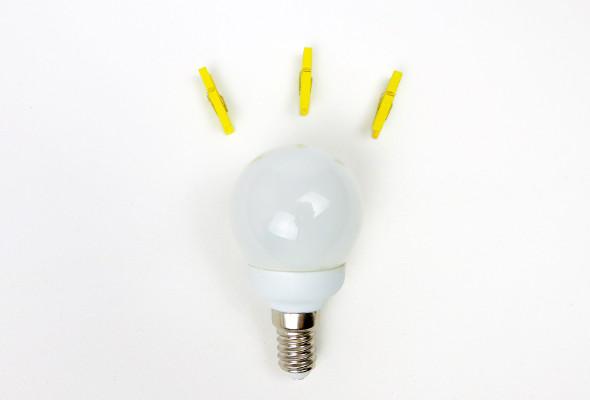 Eine Glühbirne liegt auf weißem Hintergrund. Über dieser liegen drei gelbe Wäscheklammern.