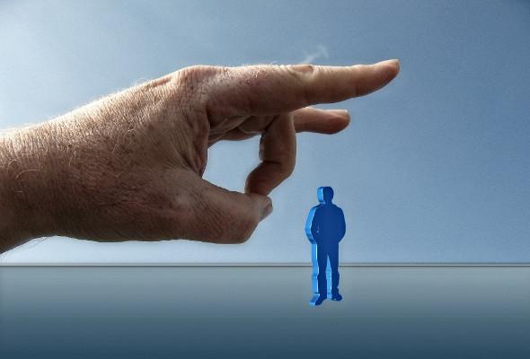 Eine große Hand schnippst ein kleines blaues Männchen weg.