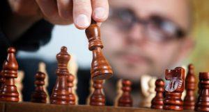 Ein Mann spielt eine Schachfigur auf einem Schachbrett.