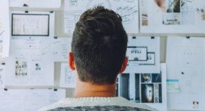 Mann sitzt vor Tafel mit Grafiken