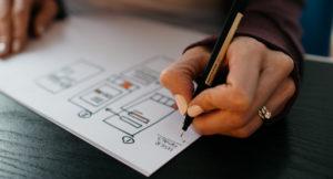 Eine Frau zeichnet auf einem weißen Papier.