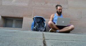Ein Mann sitzt mit seinem Laptop und seinem Rucksack auf einer Straße.