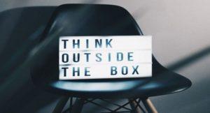 Ein Schild mit der Beschriftung Think outside the box steht auf einem Stuhl.
