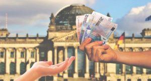 Zwei Hände vor einem Reichstagsbild. Die rechte Hand hält mehrere Geldscheine.