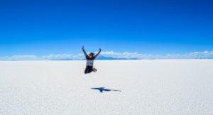 Frau springt hoch. Hintergrund: blauer Himmel und weiße Wüste.