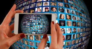 Eine Frau fotografiert ein Bildschirm mit vielen Profilen von unterschiedlichen Menschen.
